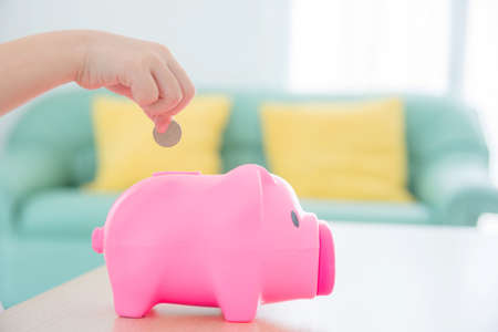 Child hand putting coin to pink piggy bank with sofa background. Standard-Bild