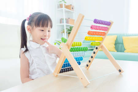 Pretty asian girl counting wood on abacus at home. Child education concept.