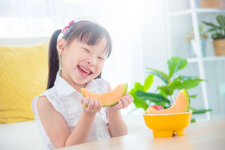 Pretty little asian girl eating melon at home. Healthy food and kid concept.
