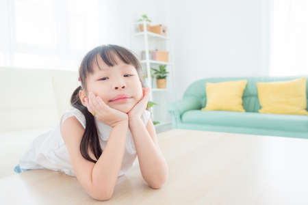 Little asian girl sitting alone in living room and looking at camera with boring face. Standard-Bild