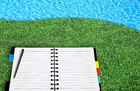 open notepad place on grass beside the blue swimming pool photo