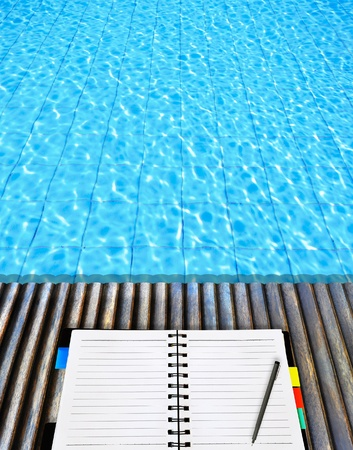 open notepad place on wood floor beside the blue swimming pool photo