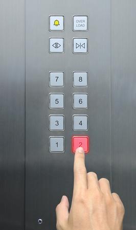 people in elevator: businessman hand press 2 floor in elevator Stock Photo