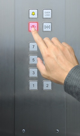 businessman hand press open door button in elevator photo