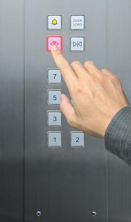 people in elevator: businessman hand press open door button in elevator