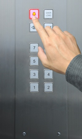 risks button: businessman hand press emergency  button in elevator Stock Photo