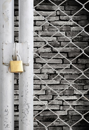 Chain link fence and metal door with lock see grunge wall background photo