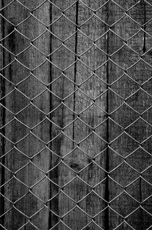 mesh fence: chain link fence see old wooden background