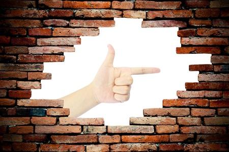 porous wall see woman hand as gun photo