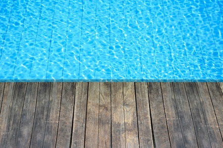 wood floor beside the blue swimming pool photo