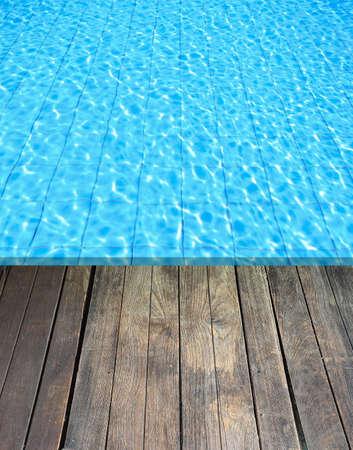 beside: wood floor beside the blue swimming pool