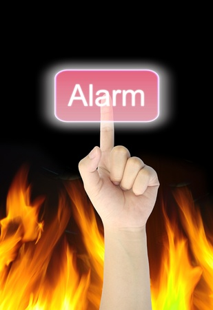 hand pressing alarm button on fire background  photo