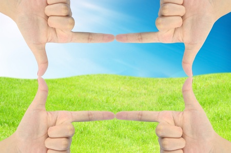 hand as frame on fresh grass and blue sky photo