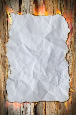 white crumpled paper and fire burn on wood background  photo