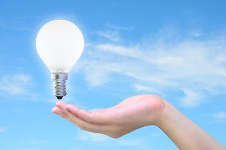 light bulb in women hand on sky Stock Photo - 9881166
