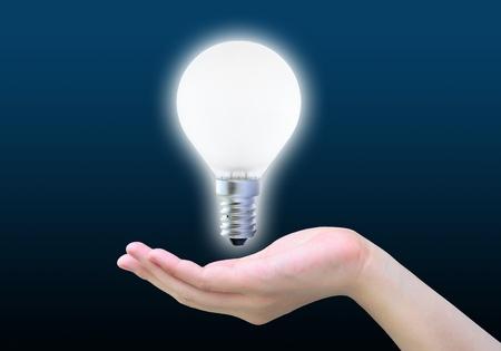 light bulb in women hand on dark photo