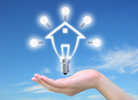 hands solution: light bulb model of a house in women hand on sky