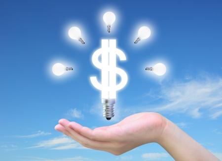 ingresos: modelo de bombilla de un s�mbolo de d�lar en mano de las mujeres en el cielo Foto de archivo
