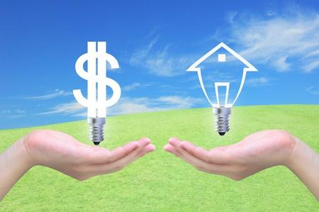 investment solutions: d�lar bombilla s�mbolo de cambio de bombillas modelo de una casa en la mano de la mujer en el cielo Foto de archivo