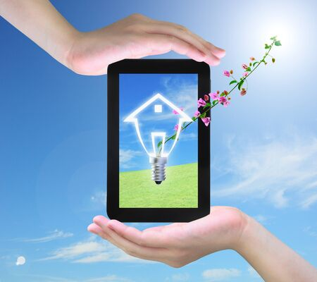 light bulb model of a house and pink flower on tablet PC in women hand photo