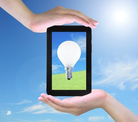 light bulb on tablet PC in women hand photo