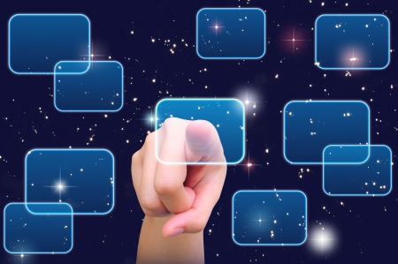 hand pushing a button on a touch screen interface under starry night sky Stock Photo