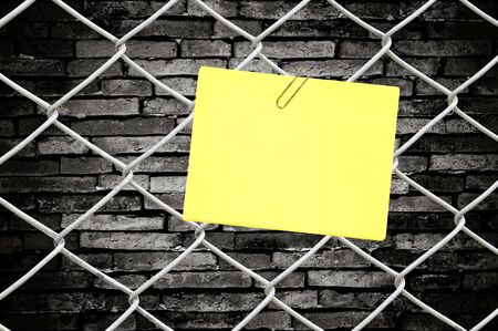 yellow note on chain link fence and old wall Stock Photo - 10132758
