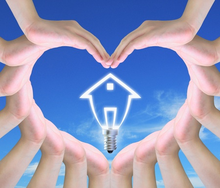 light bulb model of a house in women hands making a symbol of love  photo