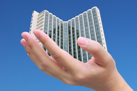 businessman hand holding a building photo