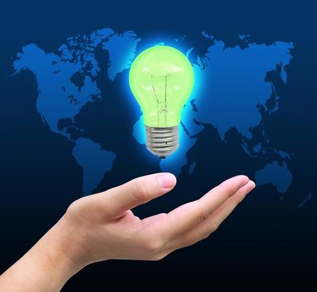 green light bulb in women hand photo