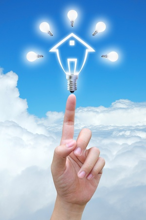 light bulb model of a house in hand on sky photo