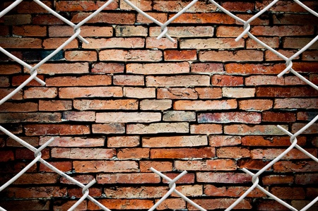 chain link fence: porous on grunge fence and wall Stock Photo