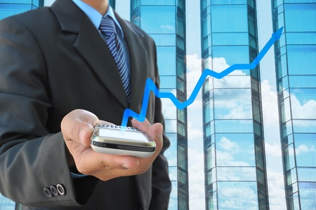businessman hand holding mobile phone and business graph photo