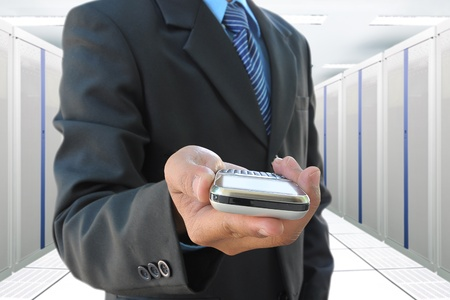 businessman hand holding mobile phone in the communication and internet network server room photo