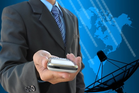businessman hand holding mobile phone and satellite dish antennas photo