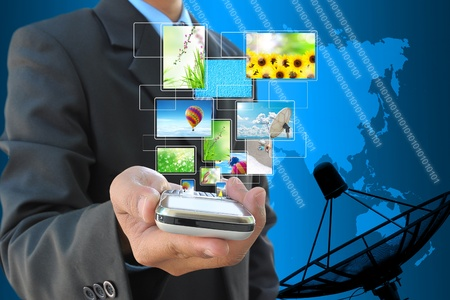 broadband: businessman hand holding streaming images virtual buttons and satellite dish antennas
