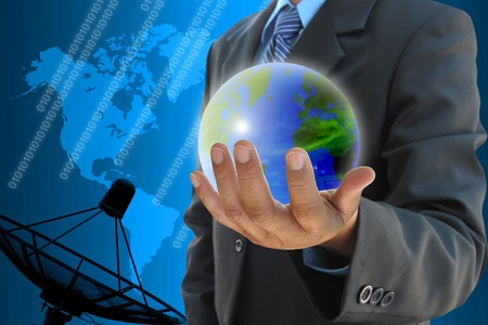 businessman hand holding a world and satellite dish antennas background photo