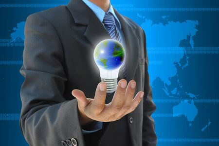 businessman hand holding the world in light bulb photo