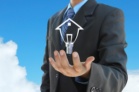 intelligent solutions: businessman hand holding a light bulb model of a house on sky