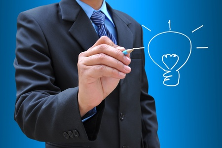 businessman hand drawing a light bulb photo