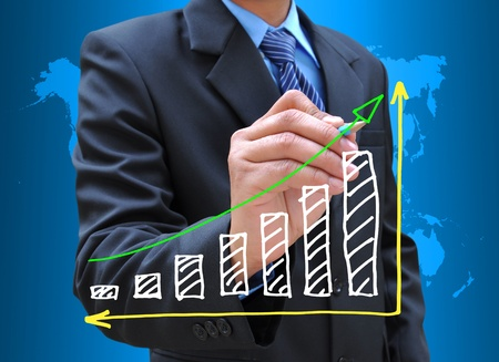 growing money: businessman hand drawing business graph