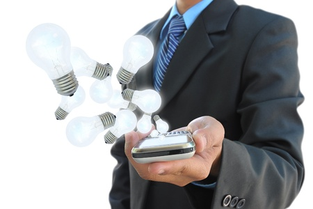 intelligent solutions: businessman hand holding mobile phone and light bulb
