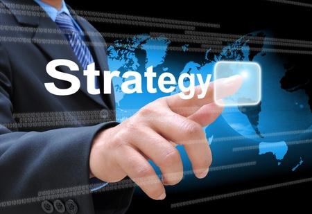 実業家の手のタッチ画面のインターフェイスの戦略ボタンを押して