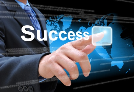 la main d'affaires de succès sur le bouton en poussant sur une interface à écran tactile