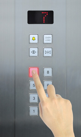 touch down: hand press 7 floor in elevator Stock Photo