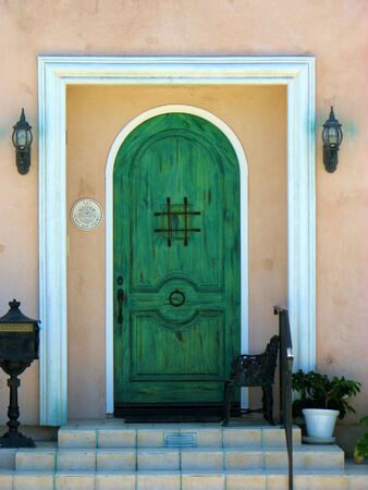 front stoop: green door arch entry entrance front door square steps stoop Stock Photo