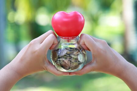 human hands saving money and do heart symbol sign Stok Fotoğraf