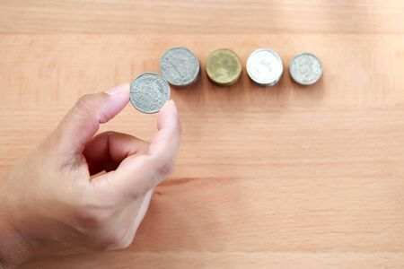 human hand saving money on stacking coins