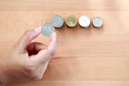 human hand saving money on stacking coins Stok Fotoğraf - 132391939