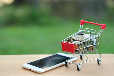 trolley with coins andcell phone on wood, idea for shopping and online payment using as business background Stok Fotoğraf - 132391944